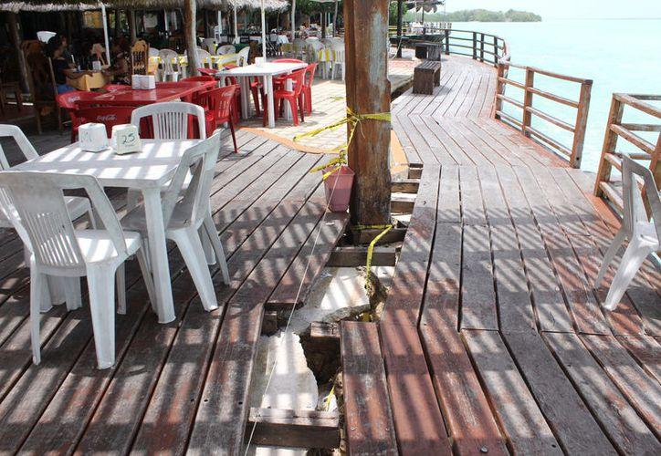 Los restauranteros han establecido señales de 'peligro' para que la gente no pise al zona afectada, y así evitar accidentes. (Joel Zamora/SIPSE)