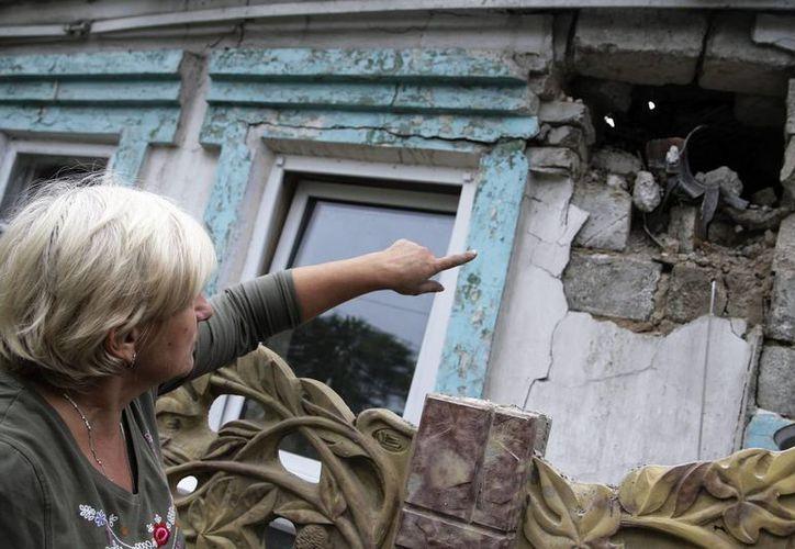 Una mujer muestra los daños en su vivienda tras ser alcanzada por un bombardeo en Donetsk, Ucrania.  De los hospitales afectados por los combates 32 no funcionan en su total capacidad y 17 fueron destruidos completamente. (EFE)