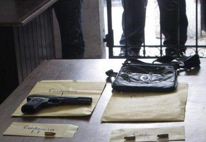 """Al """"Jimmy"""" se le decomisó una pistola nueve milímetros, cartuchos útiles, un celular y un bolso.  (Redacción/SIPSE)"""