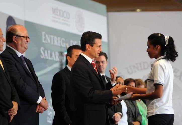 El perredista Jesús Zambrano y el gobernador Graco Ramírez (i) aparecen junto al presidente Enrique Peña durante la entrega de becas. (Notimex)