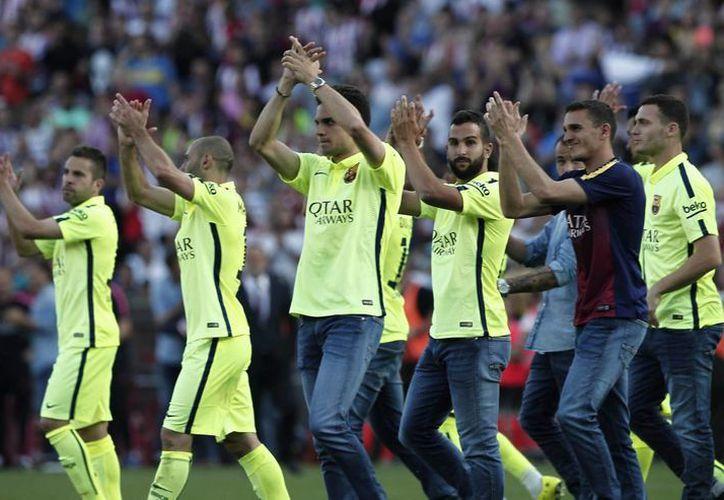 Jugadores del Barcelona celebran el haber obtenido el campeonato en la liga española. (Notimex)
