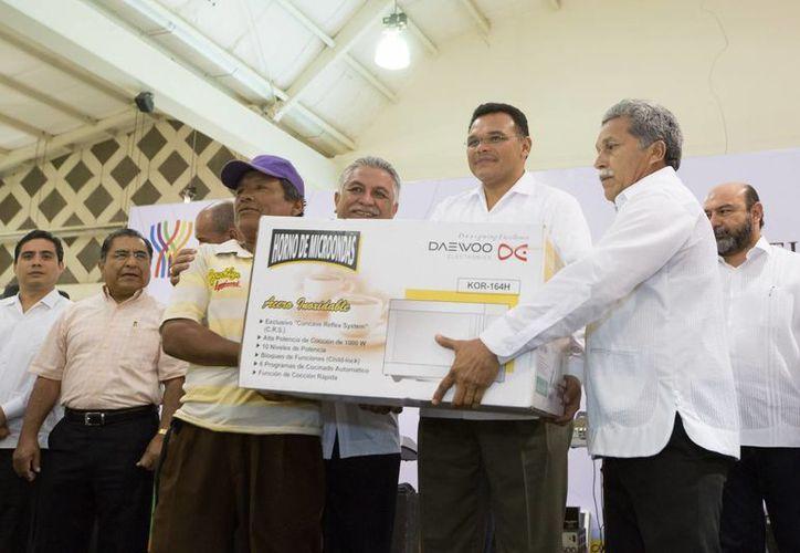 El gobernador de Yucatán, Rolando Zapata Bello, sostiene uno de los regalos que se rifaron entre los trabajadores del Poder Ejecutivo. (SIPSE)
