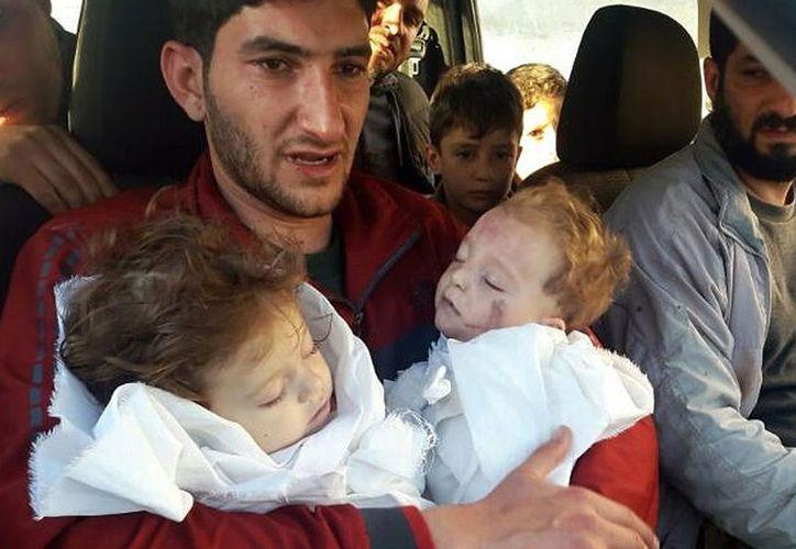 Un hombre sirio cargó a sus gemelos de nueve meses, Aya y Ahmed, uno en cada brazo. (AP).