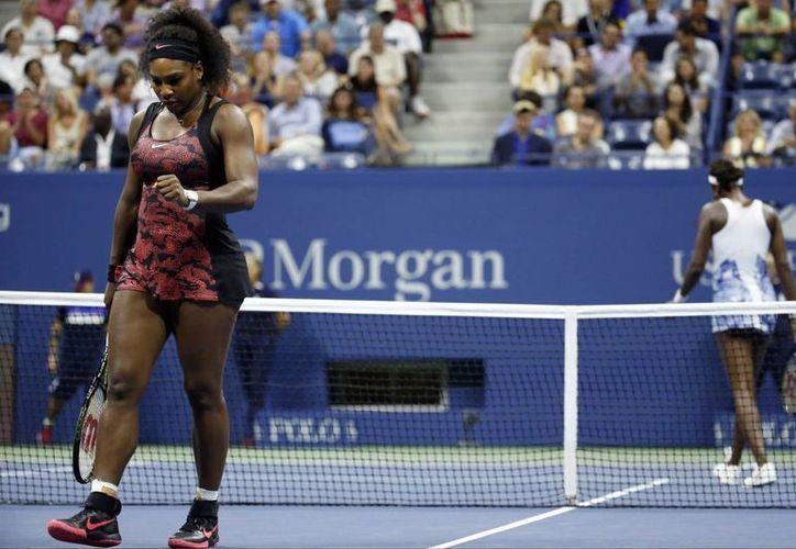 Serena Williams (i) reacciona tras disputar un punto a su hermana Venus en los cuartos de final del Abierto de Estados Unidos. Al final Serena ganó. (Foto: AP)