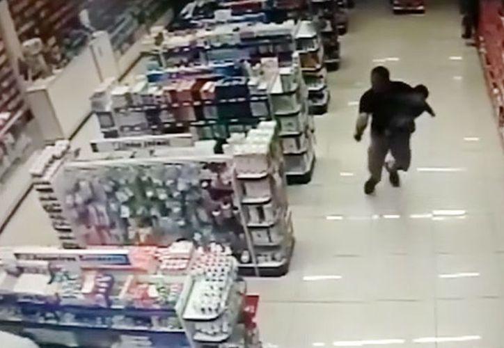 El policía disparó en al menos cuatro ocasiones contra los sujetos. (Foto: Captura)