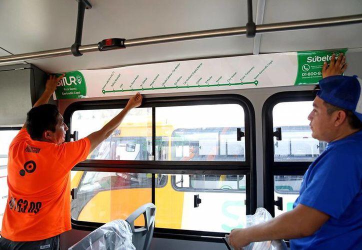 Cada ruta de autobús tendrá un color para identificarlo y en su interior habrá un cintillo donde indica el trayecto que seguirá. Trabajadores pegan las instrucciones en el interior del vehículo. (Milenio Novedades)