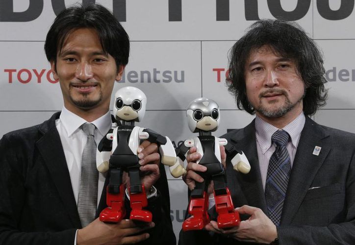 Kirobo (i) y Mirata (d), son sostenidos por Tomotaka Takahashi y Fuminori Kataoka, director general del proyecto de Toyota Motor Corp. (Agencias)