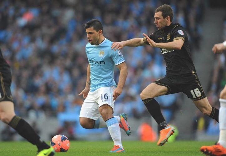 El delantero del Manchester City Sergio Agüero (c) en acción contra James McArthur, del Wigan, durante el partido disputado en el Etihad Stadium de Manchester, Reino Unido. (EFE)