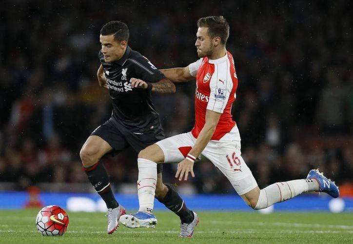Aaron Ramsey (d), disputa la pelota contra Philippe Coutinho (Liverpool) en partido de la tercera jornada de la Liga Premier que terminó 0-0. (Foto:AP).