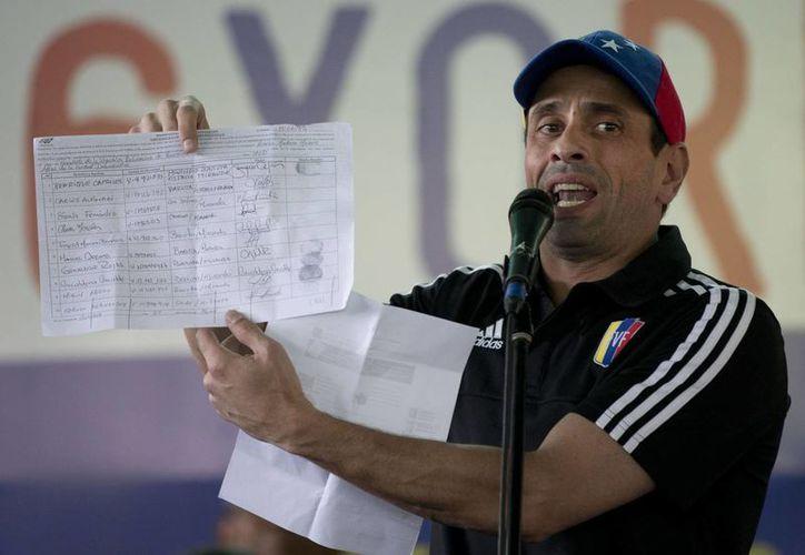 Este domingo, el líder de la oposición Henrique Capriles desestimó las amenazas del presidente venezolano Nicolás Maduro, y mostró parte de las firmas que se encuentran a favor de la revocación del mandatario. (AP)