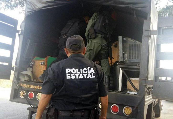Militares y agentes de la SSP suben a los vehículos oficiales los minicasinos decomisados durante los operativos. (Fátima Vasconcelos)