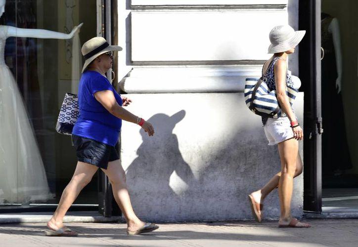El calor se mantendrá fuerte durante el día y sin lluvias. Imagen de unas mujeres paseando en el centro de Mérida. (Jorge Acosta/Milenio Novedades)
