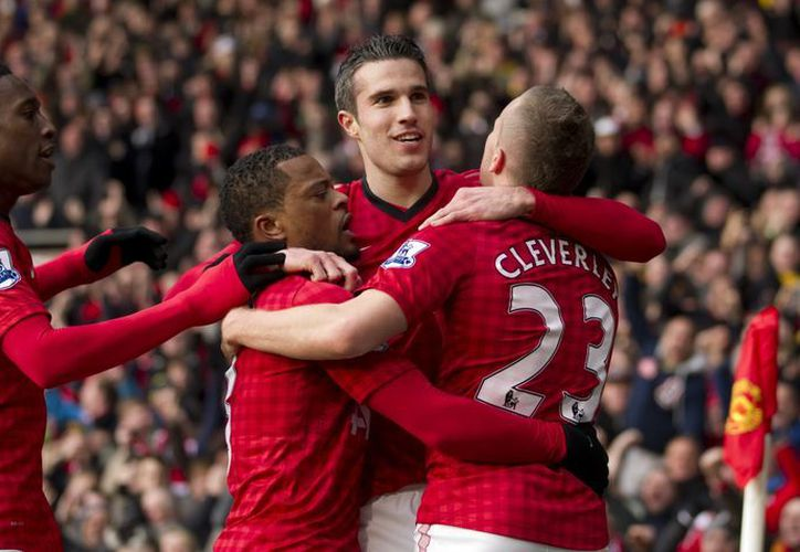 Robin van Persie (de frente) recibe la felicitación de sus compañeros tras anotar el primer gol del triunfo del Manchester. (Agencias)