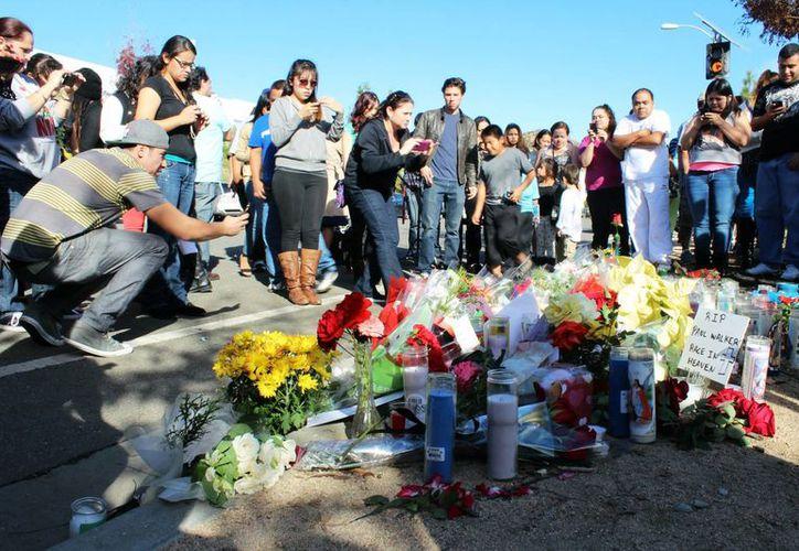 Seguidores del actor Paul Walker colocan flores y veladoras en memoria del fallecido actor, en Valencia, California. (Agencias)