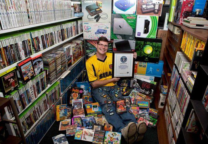 En esta fotografía del 1 de septiembre de 2013 suministrada por Brianna Blank, Michael Thomasson posa en el sótano de su casa en Buffalo, donde almacena su colección de videojuegos.(Agencias)