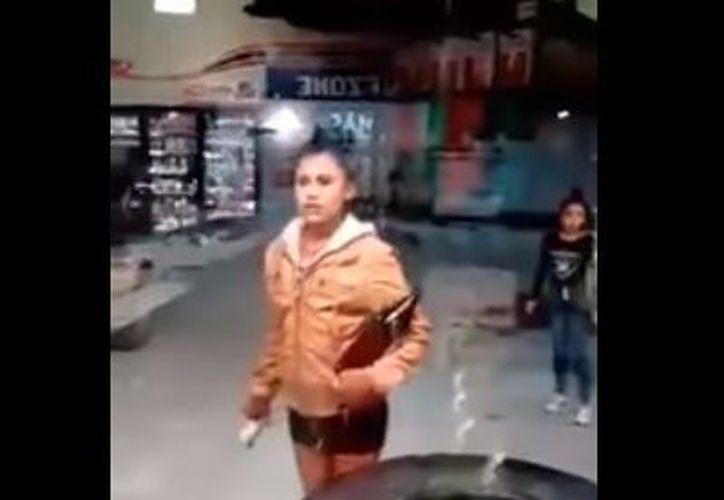 Una de las mujeres toma impulso y se avienta contra la puerta de cristal, pero falla en su intento. (Youtube)