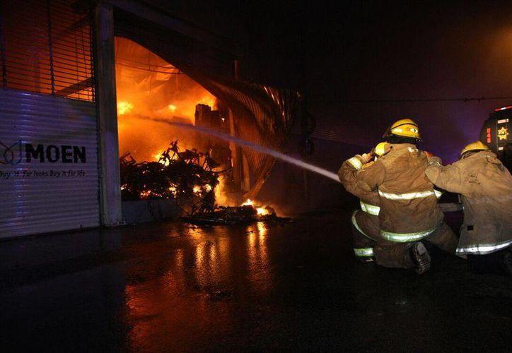 El incendio, que comenzó alrededor de las 21:00 horas, arrasó con todo lo que encontró en las bodegas siniestradas. (Martín González/SIPSE)