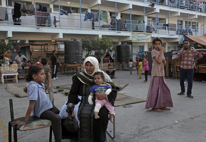 Varios palestinos desplazados que hallaron refugio en una escuela en Beit Lahiya, norte de la Franja de Gaza, esperan con ansias el anuncio del desbloqueo. (Foto AP/Adel Hana)
