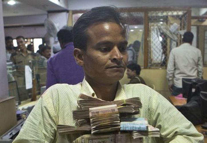 La población se apresuró a depositar el dinero en efectivo que tenía luego de que el gobierno retirase de circulación el 85 % de los billetes para combatir la corrupción. (AP/Rajesh Kumar Singh)
