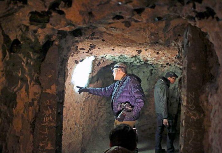 Jeffrey Gusky, a la izquierda, fotógrafo y físico de Texas, señala algunos grabados en piedra caliza en la Ciudad Subterránea de Naours, en el norte de Francia. (Agencias)