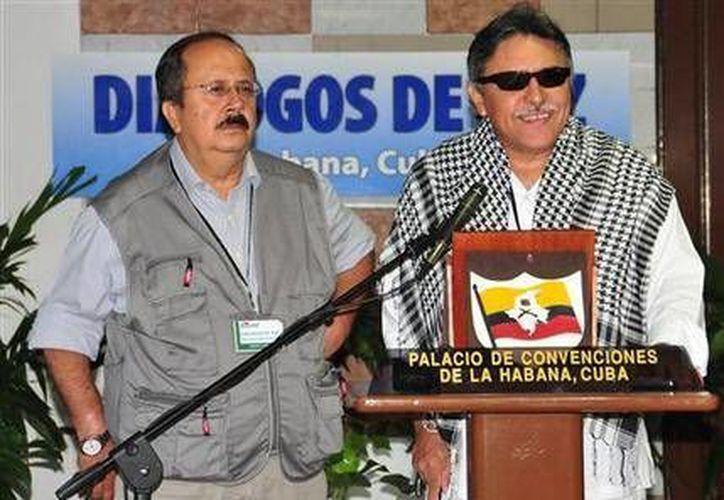 Jesús Santrich, a la derecha, delegado de las FARC, habla con la prensa acompañado de su camarada Andrés Paris al reanudarse el diálogo de paz con el gobierno colombiano en La Habana, Cuba, el lunes 12 de mayo de 2014. (Ismael Francisco, Cubadebate/AP)