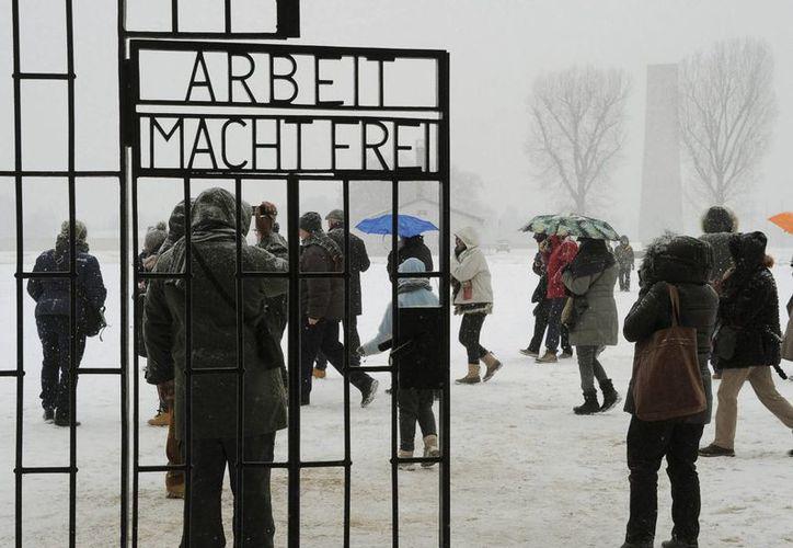 """Unas personas pasan al lado de la famosa frase """"el trabajo (te) hace libre"""" en el campo de concentración de Sachsenhausen en Oranienburg, Alemania. (Archivo/EFE)"""