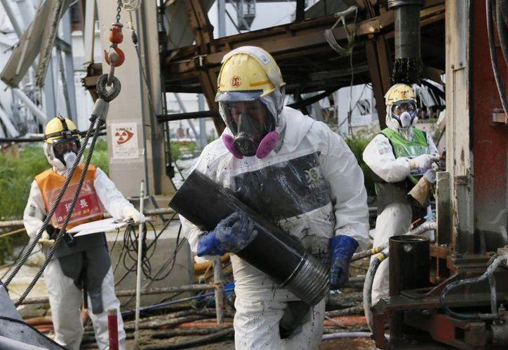 Varios trabajadores preparan tuberías heladas para construir un muro de hielo que congele el agua radiactiva en la planta Tepco, en Okuma, Fukushima. (Archivo/EFE)