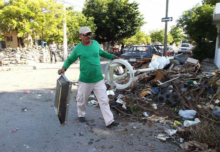 La eliminación de cacharros es clave en la lucha contra el dengue. En la imagen un hombre carga utensilio inservibles para tirar a la basura. (Milenio Novedades)