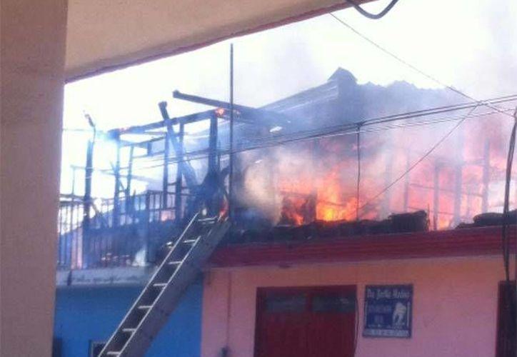 El agente de tránsito logró salvar a los menores, justamente cuando el fuego comenzaba a tomar mayor fuerza en el domicilio ubicado en el municipio de Uruapan, Michoacán.(Foto tomada de Twitter/Pcmichoacán)