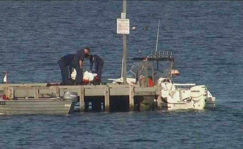 En la imagen, policias recogen los restos del hombre atacado por un tiburón en las costas de Tasmania, Australia. (Foto AP)