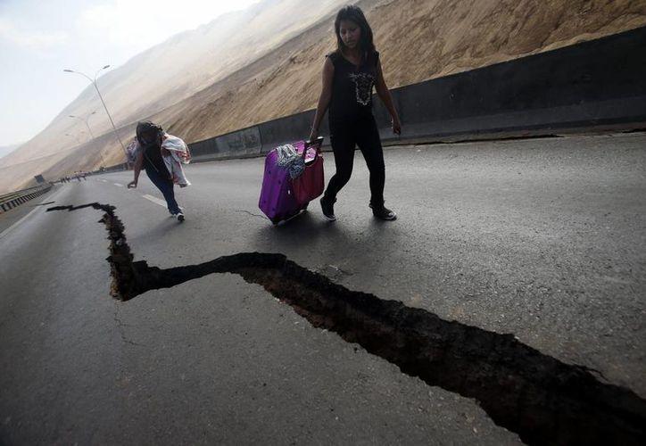 Dos jóvenes observan una grieta en el asfalto de una carretera entre las localidades de Iquique y Alto Hospicio en el norte de Chile. (EFE)