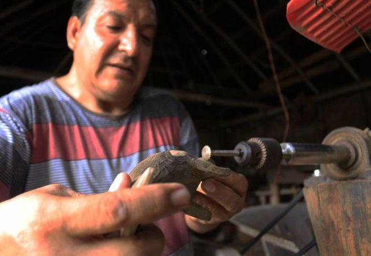 Juvencio Renato Leonor Jiménez decidió hace 30 años dedicarse a la elaboración de artesanías de madera que ahora le vende a los parques de Grupo Xcaret.  (Paloma Wong/SIPSE)