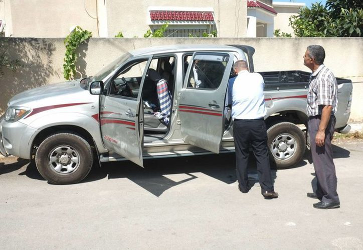 Policías tunecinos inspeccionar el coche de Mohammed Brahmi en el que fue asesinado a balazos frente a su casa. (Agencias)