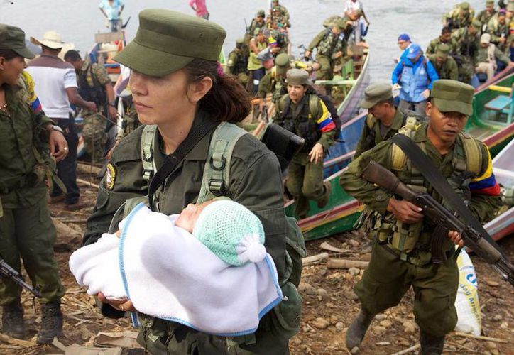 Al abrazar la reconciliación y la reincorporación a la vida civil, guerrilleros de la FARC, entre ellos una insurgente y su bebé, desembarcan en una región de Tierralta, Córdoba. (Foto Presidencia de Colombia, vía Notimex)