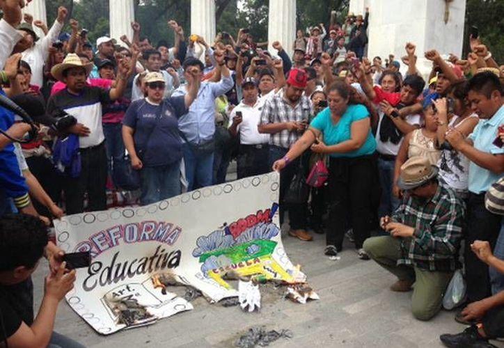 Durante el mitin, los maestros hicieron una quema simbólica de la Gaceta Parlamentaria en rechazo de la reforma educativa. (Fanny Miranda/MILENIO)