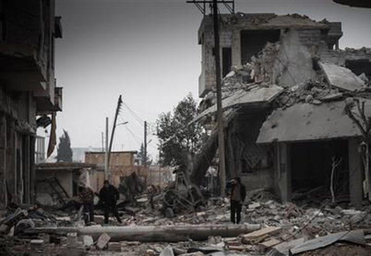 En grupo de civiles sirios inspecciona la destrucción de edificios tras los bombardeos de la Fuerza Aérea de Siria en la villa de Binnish, Siria. (Agencias)