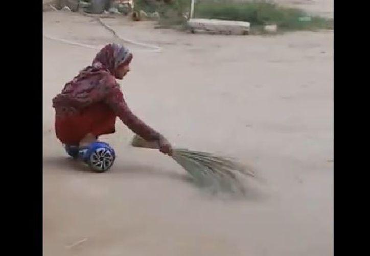 En cuclillas, la mujer paquistaní emplea un deslizador Hoverboard para limpiar su patio. (Foto: Captura)