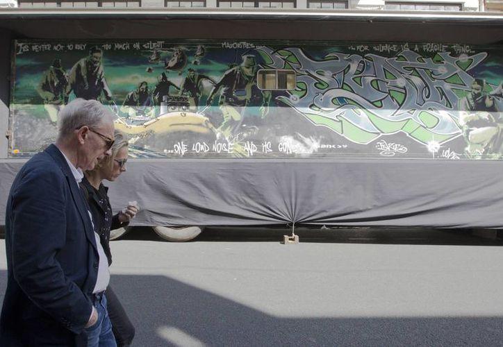 Personas caminan en París frente a un remolque en el que el artista callejero británico Banksy pintó una obra llamada 'Silent Majority'. La obra es exhibida frente a la casa de subastas Digard. (AP)