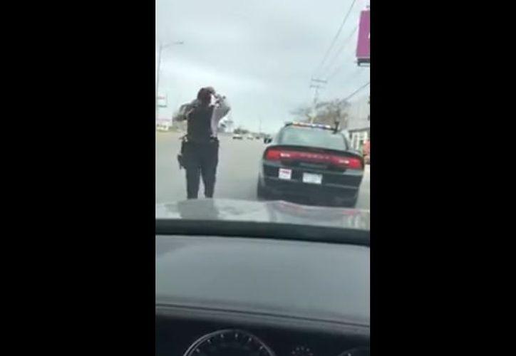 Imagen de uno de los dos oficiales agredidos acercándose al vehículo BMW. (Youtube)