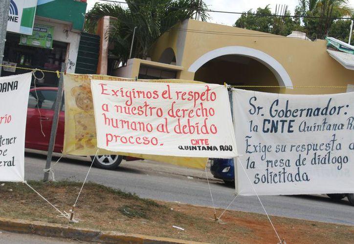 En las mantas reclamaban jueces justos en Quintana Roo y recalcando que no es obligación de los padres mantener las escuelas. (Foto: Jesús Caamal / SIPSE)