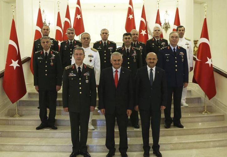 Fotografía facilitada por la Oficina de Prensa del Primer Ministro turco que muestra al primer ministro turco, Binali Yildirim (c), y al jefe del Estado Mayor, Hulusi Akar (c), junto a los miembros del Consejo Supremo Militar turco tras su reunión en Ankara, Turquía. (EFE)