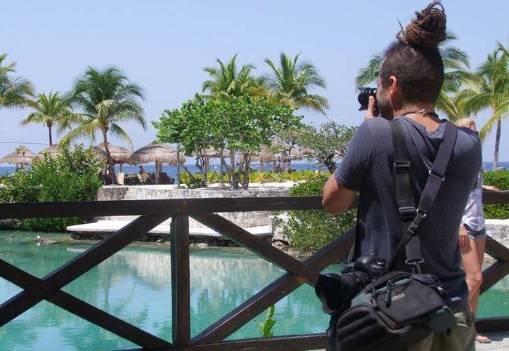 El fotógrafo y el editor del libro conmemorativo de Fonatur, contemplan a la Marina Cozumel para la publicación.  (Redacción/SIPSE)