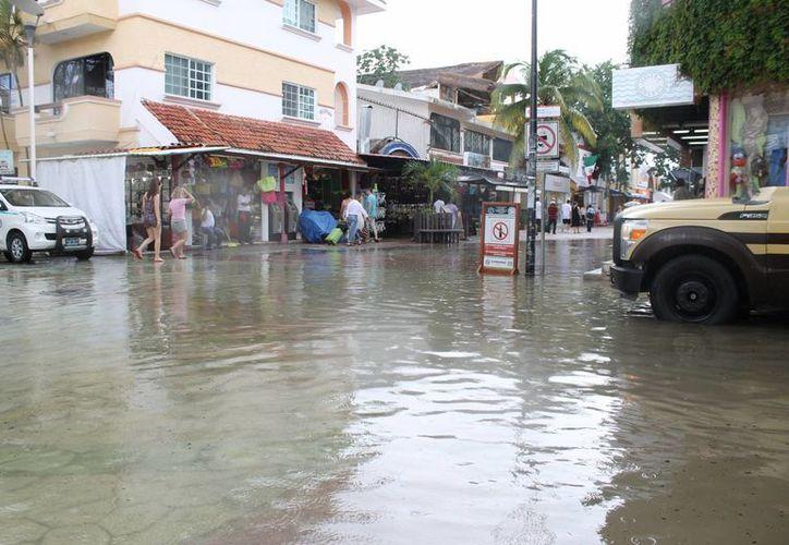Las calles del centro turístico de Playa del Carmen lucieron cubiertas de agua tras la fuerte lluvia que cayó ayer.  (Juan Cano/SIPSE)