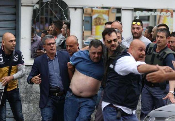 Los agentes tuvieron que custodiar a Giulo Murolo (c), ya que decenas de vecinos intentaron lincharlo. (Ansa)