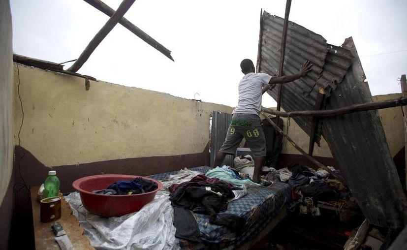 Un residente de Haití realiza reparaciones a su casa luego del paso del huracán Matthew. (Foto AP / Dieu Nalio Chery)