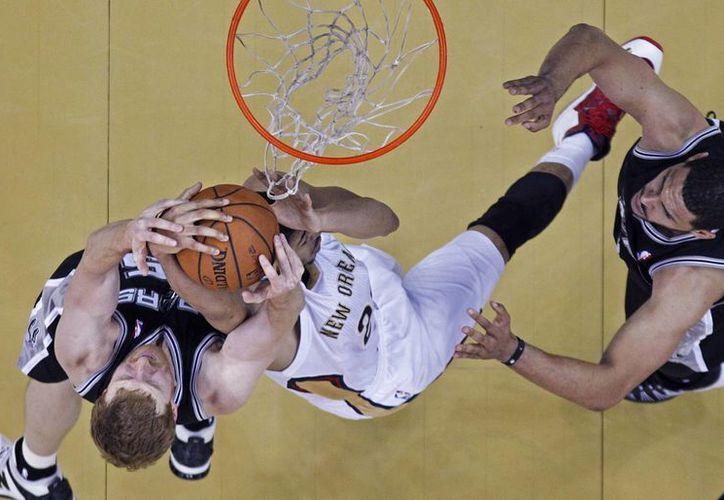 Anthony Davis (c) de los Pelicans, forcejea con Matt Bonner, de Spurs mientras los observa Jeff Ayres (d). (Agencias)