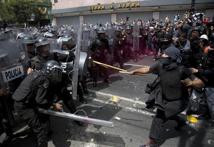 El primer enfrentamiento entre manifestantes y policías se registró en la avenida Juárez. (AP)