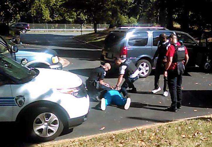 En esta imagen tomada de vídeo grabado por la esposa de Keith Lamont Scott, Rakeyia Scott, se ve a un agente de Charlotte en cuclillas junto a la víctima. (Rakeyia de Scott/Curry bufete de abogados a través de AP)