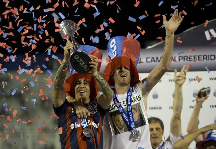 Leonardo Romagnoli (izquierda), del San Lorenzo, alza el trofeo del Inicial argentino. A su izquierda aparece su compañero Juan Mercier. (Agencias)