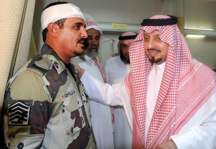 Fotografía facilitada por la por la agencia oficial saudí SPA, que muestra al gobernador de la provincia de Asir, el príncipe Faisal bin Khalid (d), mientras visita a uno de los soldados que resultaron heridos en un ataque contra una mezquita en Abha. (EFE)